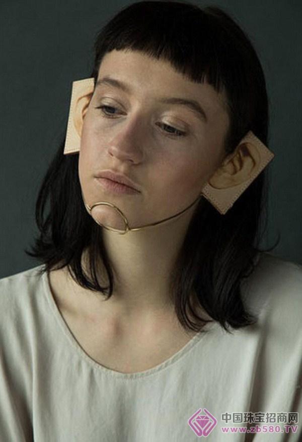 据英国《每日邮报》8月16日报道,29岁的日本设计师亚纪子新里(Akiko Shinzato)攻读英国中央圣马丁艺术与设计学院的珠宝设计专业,为该学位交了一份让人眼前一亮的毕业作业。在这份名为另一种皮肤的作品集中,亚纪子使用珠宝代替化妆品,用印着五官的皮革制品来代替整容手术。这些脸部饰品分别价值200至600英镑(约合人民币2000至6000元)不等。 亚纪子的作品可分为两部分:一部分是以小丑的脸部彩绘为理念,把珠宝架在脸上作为装饰。例如在眼睛上架上两块蓝宝石,鼻尖上顶一个粉宝石,再在脸颊上悬