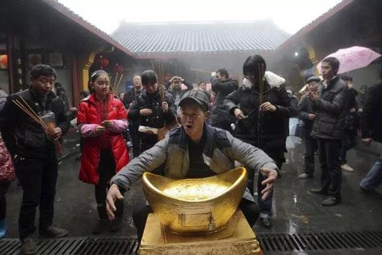 浙江杭州财神庙内,一名男子抱着金元宝求新年财运。