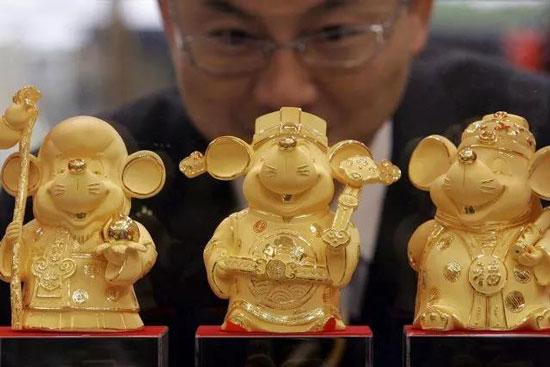 中国香港一家金店的员工正在摆出纯金的鼠年吉祥物。