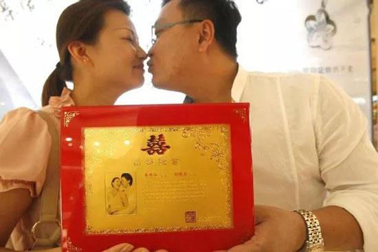 一对结婚十年的夫妇在结婚纪念日定制纯金结婚证。